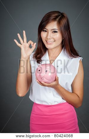 Beautiful Asian Girl Show Ok Sign With A Pink Pig Money Box