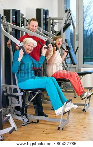 Happy Old Women At The Gym Assisted By Instructor