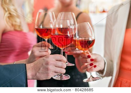 Friends Tossing Glasses Of Red Wine