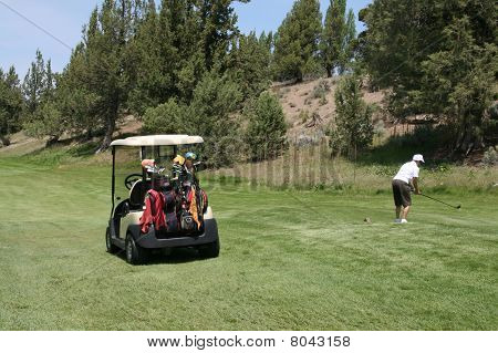 Golf Cart Waits While A Lady Golfer Hits The Ball