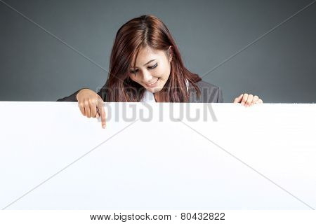 Asian Businesswoman Stand Behind A Blank Banner , Point Down And Smile
