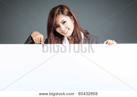 Asian Businesswoman Stand Behind A Blank Billboard , Point Down And Smile