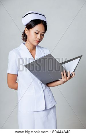 Young Asian Nurse Read Data In A Ring Binder