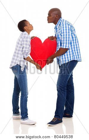 african couple with paper heart symbol giving each other air kiss
