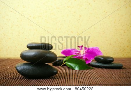 Massage stones and orchid in the background