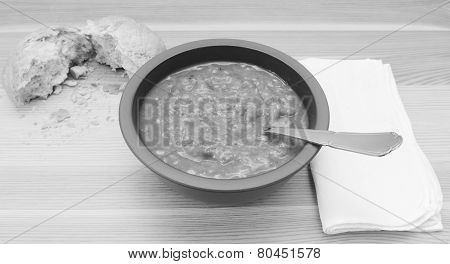 Soup On A Table With A Torn Bread Roll