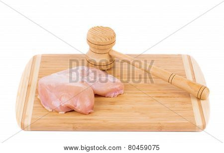 Raw chicken breast and mallet