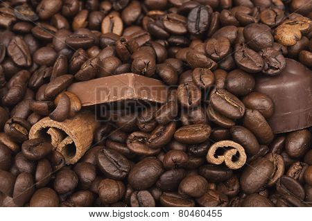 Close Up Of Piled Coffee Beans, Cinnamon Sticks And Chocolate