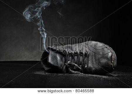 Old work shoe in smoke