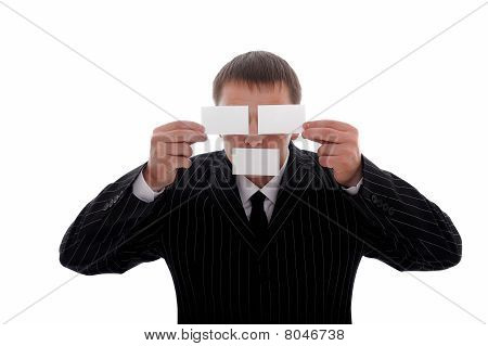Businessman covering his eyes and mouth with business cards