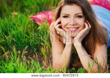Young happy woman in the summer on the green meadow