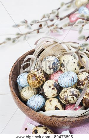 Colorful chocolate easter eggs in wooden bowl