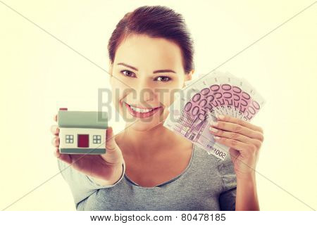 Young casual woman with money and house.