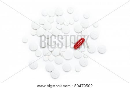 Red pill on heap of  white tablets, isolated