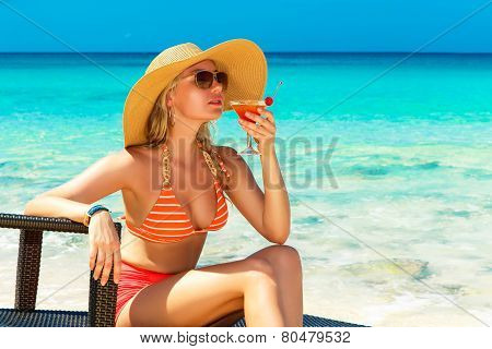 Beautiful Young Girl In Bikini Is Sitting On A Sun Lounger Coast Of Tropical Sea