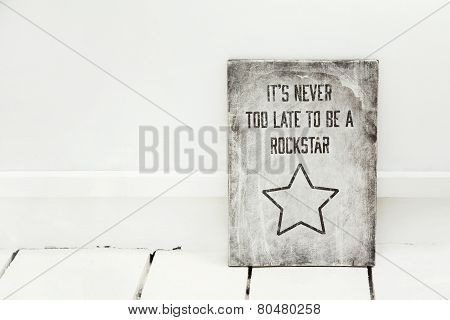 Motivational wood sign on the white floor IT'S NEVER TOO LATE TO BE A ROCK STAR.