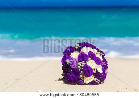 Wedding Bouquet Lying On The Sand On A Tropical Beach. Blue Sea In The Background.