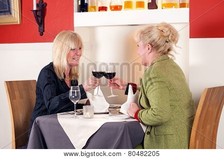 Two Blond Woman Toasting With Red Wine