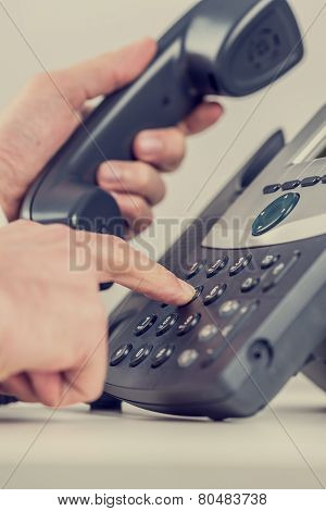 Retro Image Of A Businessman Dialing A Phone Number