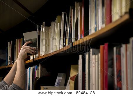 Man Taking Book In Lig´brary
