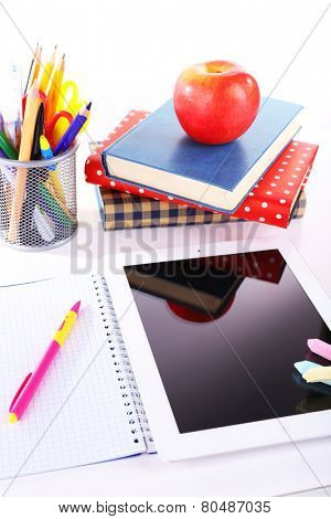 Pile of books with tablet on white background