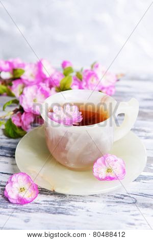 Beautiful fruit blossom with cup of tea on table on grey background