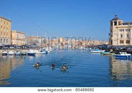 SIRACUSA, ITALY - JENUARY 17: fishing boats and kayakers in the darsena of Ortigia Islet from the Bridge Umbertino. On the background the skyline of Siracusa on the mainland. Shot in 2015