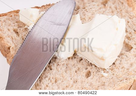 Detail Of A Knife Spreading Cheese On A Bread Slice On White Background
