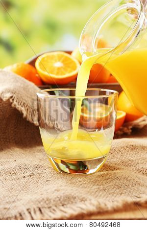 Pouring orange juice from glass carafe, on wooden table and bright background