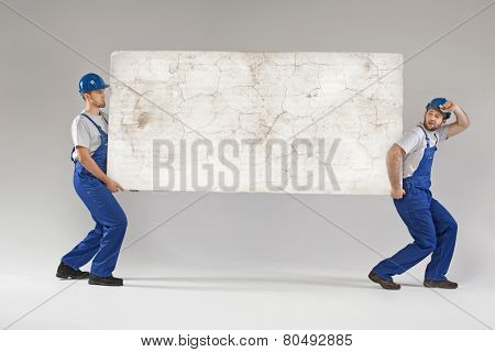 Three employees holding white board