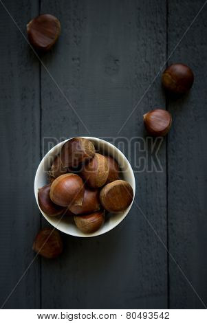Raw chestnuts in a white bowl -top view