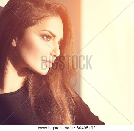 Sideways portrait of young beauty romantic girl looking away, close-up. Tender glance of beautiful brunette make-up woman in sun light.