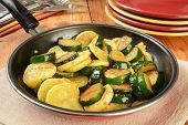 stock photo of zucchini  - Sauteed summer and zucchini squash in a frying pan - JPG
