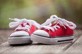 foto of baby feet  - cute red baby sneakers on wooden background - JPG