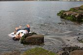 image of accident victim  - View of a young woman washed up on rocks at the edge of a river possible boating accident victim - JPG