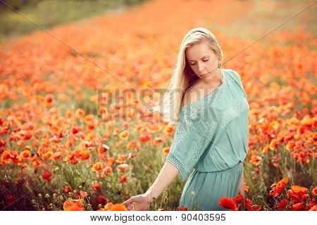 Beautiful woman on poppy flower field