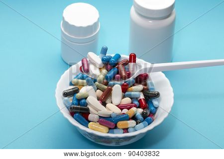 Different pills on a plate and two bottle