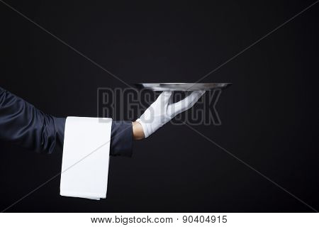 Image of a waiter hand holding a tray on dark background