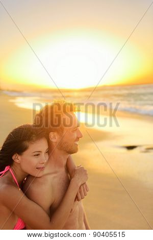 Happy romantic couple lovers on beach honeymoon having playful fun together during summer beach holidays. Cheerful young multiracial couple, Asian woman and Caucasian man. From Oahu, Hawaii, USA.