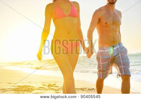 Summer beach couple romantic holding hands at sunset walking in love on honeymoon travel vacation holidays. Unrecognizable woman and man in happy romance wearing bikini and casual beachwear shorts.
