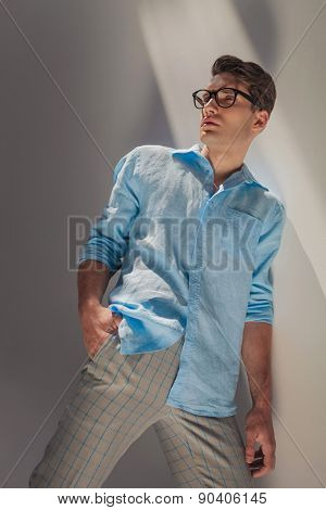 Angle view of a casual fashion man holding his hand in pocket while leaning on a wall