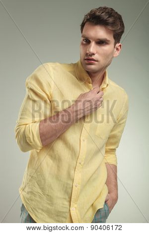 Attractive young business man holding his hand in pocket while closing his yellow shirt.