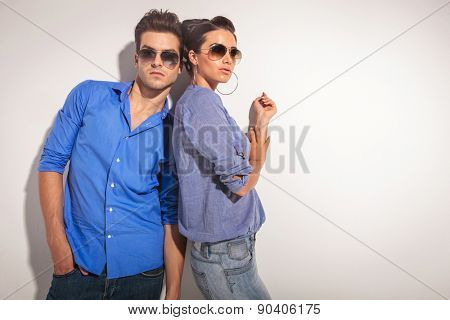 Beautiful fashion woman leaning on a wall while her lover is looking at the camera.