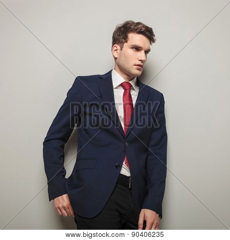Side view of a business man leaning on a grey wall while looking away fom the camera.