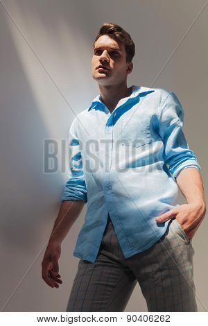 Angle view of a fashion man leaning on a grey wall, holding his hand in pocket.