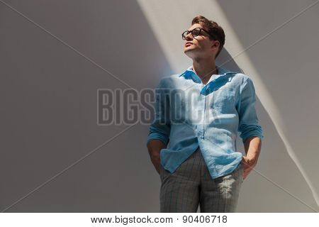 Portrait of a handsome young casual man leaning on a grey wall while holding his hand in pockets.