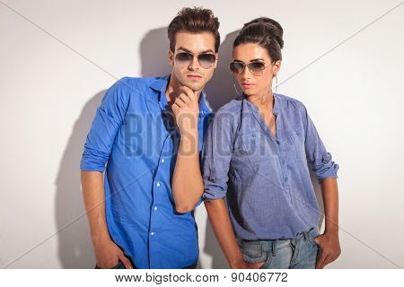 Attractive young man holding his hand to his chin while his lover is looking at the camera.