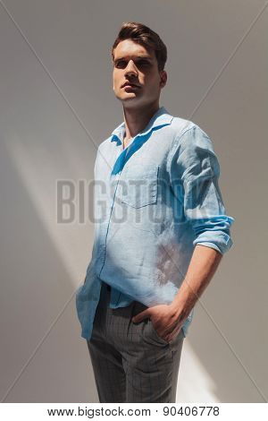Attractive young fashion man posing with his hand in pocket on grey studio background.