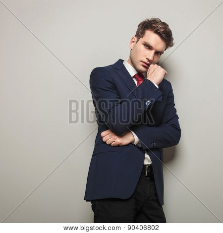 Young business man leaning on a grey wall while thinking on something important.