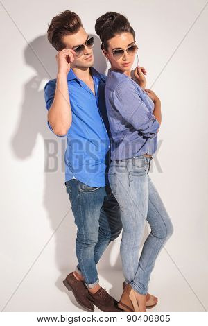 Side view of a casual couple posing near a grey wall, he is fixing his glasses while she is looking down.
